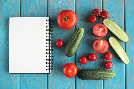 composition book: Note book and composition of vegetables on blue wooden desk. Tomato, cucumber. Top view.
