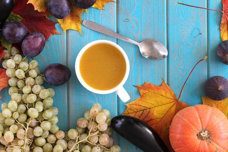 Soupe de potiron dans une tasse blanche sur la table bleue. Composition de la récolte. Banque d'images