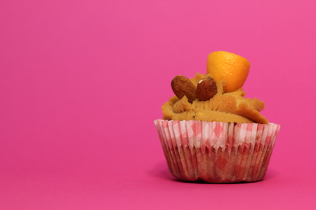 Cream caramel cupcake on pink background decorated by almonds
