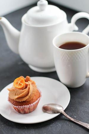 A teapot, a cup of tea and a caramel cupcake. Modern photo.