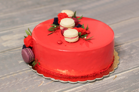 Tasty red homemade cake decorated by red candies and macarons Stock Photo