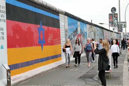 BERLIN, GERMANY - JUNE 2018: Graffiti and artworks at the East Side Gallery on June 02, 2018 in Berlin, Germany. People visit urban art of East Side Gallery at public street in Berlin. Editorial