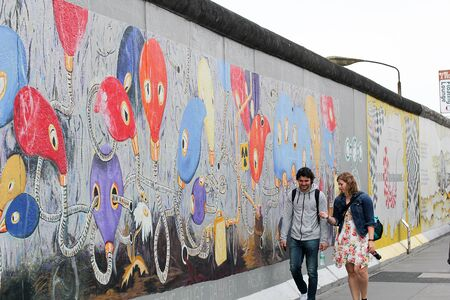 BERLIN, GERMANY - JUNE 2018: Graffiti and artworks at the East Side Gallery on June 02, 2018 in Berlin, Germany. People visit urban art of East Side Gallery at public street in Berlin. Imagens - 131611381