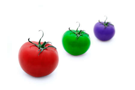 Conceptual illustration of three tomatoes in RGB colours over white background. Shallow depth of field.