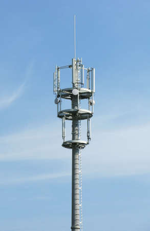 GSM aerial mast over blue sky in a sunny day. Telecommunication industry. Stock Photo