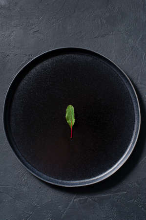 Chard on a black plate, minimalism, concept. Dark background, top view, space for text Stock Photo