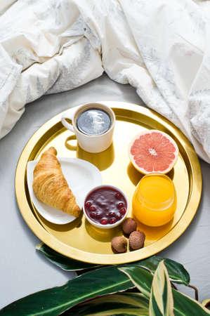 Breakfast in bed, hotel service. Coffee, jam, croissant, orange juice, grapefruit, lychee. Top view, light background