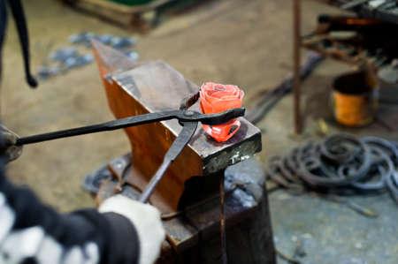 Blacksmith forges steel rose on the anvil Standard-Bild