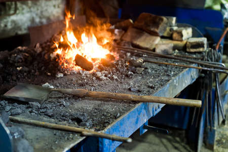 The blacksmith melt metal in a furnace, an authentic forge