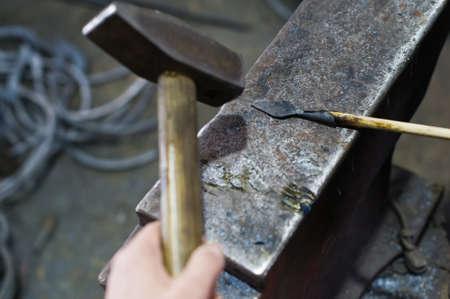 The blacksmith forges an arrowhead hammer on the anvil