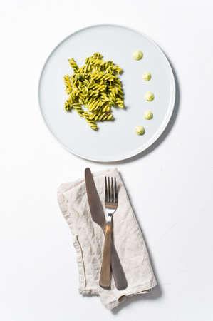 Gluten-free pasta with spinach. Diet dish. Minimalism. White background, top view