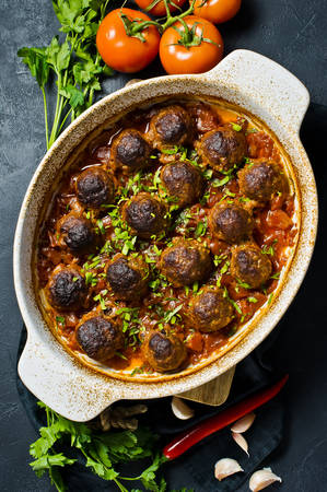 Swedish meatballs in tomato sauce in a baking dish. Black background, top view