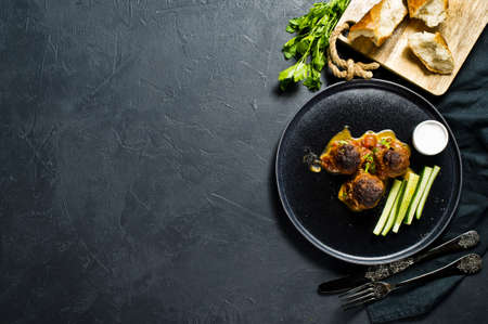 Swedish meatballs in tomato sauce on a black plate, cucumbers, salt, bread. Black background, top view, space for text