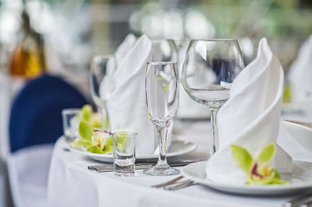 Table with glasses, plates and white napkins, green flower, dinner in the restaurant
