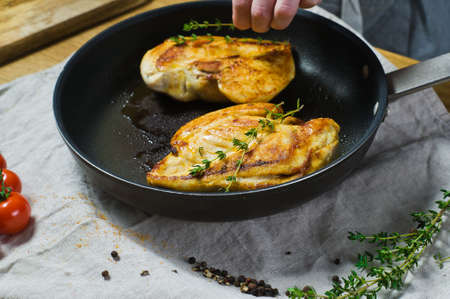Chef sprinkles thyme on chicken Breasts in a frying pan. Background kitchen, side view Banque d'images