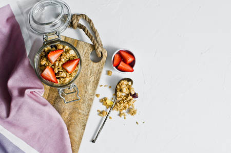 Home granola with strawberries in a glass jar. White background, top view, space for text. Healthy vegan snack