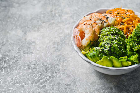 Buddha bowl with shrimps, avocado, carrot, brocoli and rice. Gray background, side view, space for text Zdjęcie Seryjne