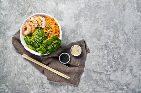 Buddha bowl with shrimps, avocado, carrot, brocoli and rice. Balanced food. Gray background, top view, space for text Banco de Imagens
