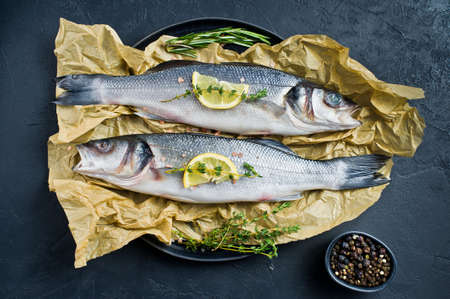 Raw sea bass with rosemary, thyme and lemon. Black background, top view