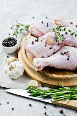 Raw chicken legs. Ingredients for cooking: rosemary, thyme, garlic, pepper. Gray background, side view