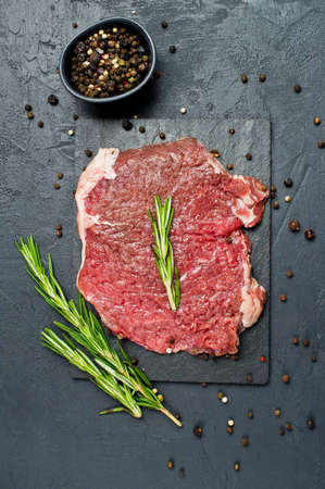 Raw beef flank steak on a stone Board with rosemary. Black background, top view, space for text
