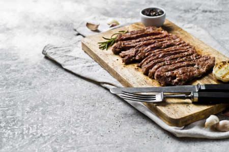 Sliced BBQ steak on wooden chopping Board. Gray background, top view, space for text Archivio Fotografico