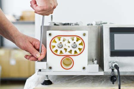 worker repairs industrial dispenser, food industry
