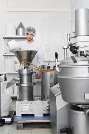 30.03.2019 Rusia, San Petersburgo - trabajador colocando chips de coco en una trituradora industrial - prensa. Producción de aceite de coco, pasta.