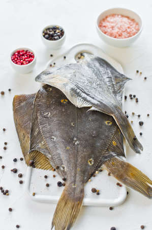 Raw plaice, ingredients for cooking. White background, top view
