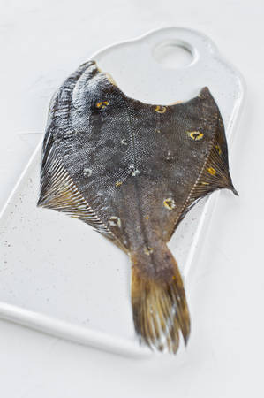 Raw plaice. White background, side view