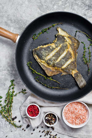 Fried plaice in a pan. Gray background, top view