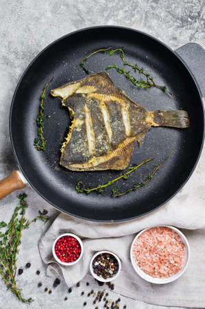 Fried flounder in a pan. Gray background, top view Stock Photo