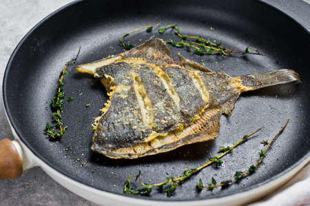 Fried flounder in a pan. Gray background, top view Banque d'images