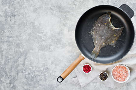 Raw flounder in the pan. Gray background, top view, space for text