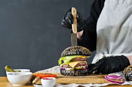 The chef sticks a knife in the Burger. The concept of cooking black cheeseburger. Homemade hamburger recipe. Kitchen, side view, space for text