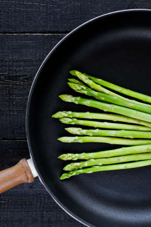 Green asparagus in the pan. Black background, top view, space for text