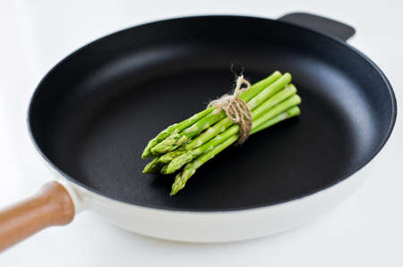 Organic mini asparagus. White background, top view, space for text