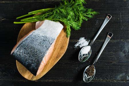 Atlantic raw salmon, steak and parsley sprig on black wooden background. Reklamní fotografie