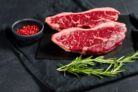 Raw beef ramp steak. Black background, top view Imagens