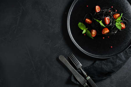 Black spaghetti with Basil and cherry tomatoes, vegetarian pasta. Black background, top view, space for text