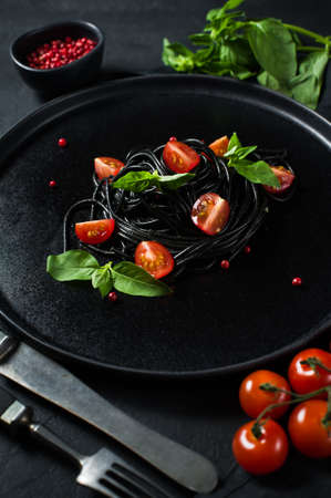 Balanced healthy food, black spaghetti with Basil and cherry tomatoes, vegetarian pasta. Black background, top view, space for text Stok Fotoğraf