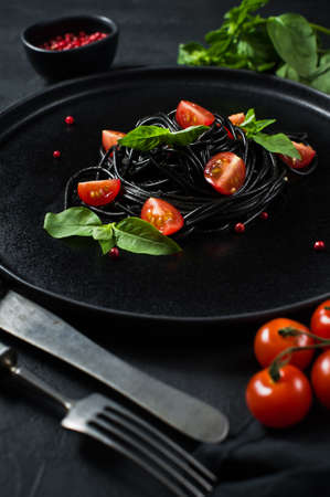 Vegetarian dish, black spaghetti with Basil and cherry tomatoes. Black background, top view