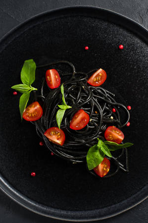 Black vegetarian pasta with Basil and cherry tomatoes. Black background, top view
