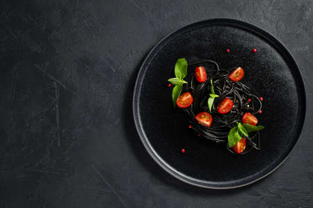 Fried mackerel in a pan. Black background, top view, space for text
