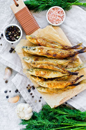 Fried mackerel on a wooden chopping Board, dill, pink salt, pepper and garlic. Gray background, top view, space for text