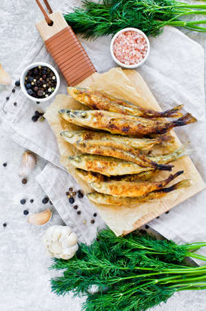Fried smelt on a wooden chopping Board, dill, pink salt, pepper and garlic. Gray background, top view, space for text