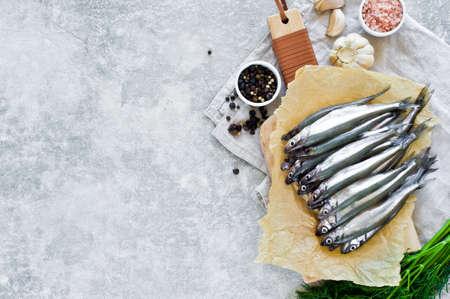 Rohe Makrele auf einem Schneidebrett aus Holz, Dill, rosa Salz, Pfeffer und Knoblauch. Grauer Hintergrund, Draufsicht, Platz für Text Standard-Bild