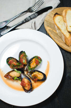 Baked mussels in tomato sauce with coriander and Parmesan on a white plate