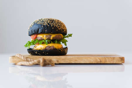 Black Burger on wooden chopping Board, grey background Banque d'images - 121254197