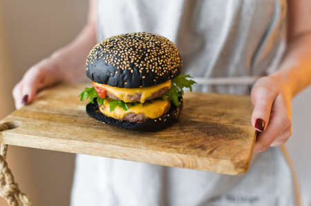 Girl chef holds in her hands a wooden cutting Board with a black cheesburgers.